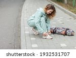Small photo of Fitness woman tying shoelaces outdoors