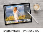 Concept of digital photo editing on tablet computer with wireless stylus pen