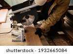 Small photo of Miter saw with a large metal blade in the hands of a carpenter. Working tool for sawing wooden planks. A close-up of the sawing process. Labor protection and safety rules for the use of power tools.