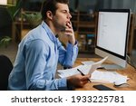 Small photo of Pensive attractive young entrepreneur looking through paperwork while sitting at the desk