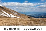 A panoramic view on an Alpine chain in Austria, partially covered with snow. The vast pasture has golden colors. There are other chains in the back. A narrow pathway leading to the top. Overcast