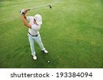 Small photo of High overhead angle view of golfer hitting golf ball on fairway green grass