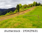 summer landscape. fence near the meadow path going up on the hillside. forest in fog on the mountain. - stock photo