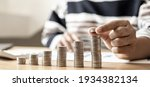 Small photo of Women are stacking coins on top of the coin pile on the highest row. Placing coins in a row from low to high is comparable to saving money to grow more. Money saving ideas for investing in funds.