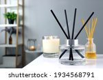 Small photo of luxury glass aroma scent reed diffuser bottle is used as air freshener on the table with scented candle in the nice white living room to creat relax , cozy and clean ambient and for decoration