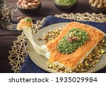 Small photo of Arabic Cuisine; Traditional Middle Eastern Cheese Kunafa Dessert. A delicious pastry consisting of soft melty cheese and shredded phyllo dough. Served with sugar syrup and crushed pistachio.
