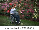 Beautiful young woman in a wheelchair visiting a rose garden in Oregon. - stock photo