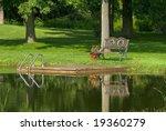 Bench Beside Pond In Summer