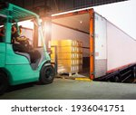 Forklift Tractor Loading Package Boxes into Cargo Container. TrailerTruck Parked Loading at Dock Warehouse. Shipment Delivery Service. Shipping Warehouse Logistics. Freight Truck Transportation.