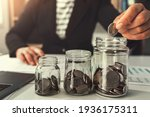 Small photo of saving money with hand putting coins in jug glass concept financial