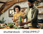 Small photo of Black man blending healthy food while preparing smoothie with is wife in the kitchen.