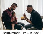 Small photo of Male gay couple with adopted baby girl at home - Two handsome dads feed the baby girl on kitchen - Male babysitters - Lgbt family at home - Diversity concept