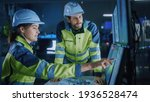 Small photo of Industry 4.0 Modern Factory: Project Engineer Talks to Female Operator who Controls Facility Production Line, Uses Computer with Screens Showing AI, Machine Learning Enhanced Assembly Process