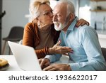 Small photo of Mature woman kissing her mature husband while he uses a computer at home