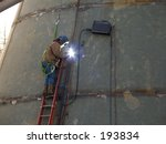 This is a shot of a man welding on a ladder. - stock photo