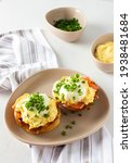 Small photo of Delicious hearty breakfast, eggs Atlantic in a plate on a white background, round fried bun with salmon and eggs Benedict, hollandaise sauce and green onions