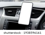 Small photo of Mobile phone on the car air vent.Blank with white screen.Mock up smart phone in car.
