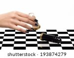 Beautiful woman hand with luxury nails in black and white playing chess. Manicure and nail art concept. Closeup portrait isolated on white - stock photo