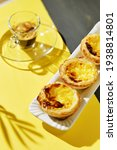 Small photo of three custards (Pasteis de nada) and an glassy espresso cup in the bokeh of the baclkdrop. colors yellow grey