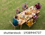 High angle view of caucasian three generation family sitting at table eating meal in garden. three generation family celebrating independence day eating outdoors together.