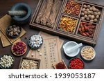 Small photo of Ancient Chinese medicine books and herbs on the table.English Translation:Traditional Chinese medicine is used in the prevention and treatment of diseases, has the function of rehabilitation.