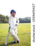 Small photo of Boy in cricket uniform holding a cricket bat