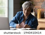 Small photo of Diligent aged student. Focused elderly hispanic woman in headphones watch webinar on laptop screen take notes to paper notebook. Mature old lady in headset study online take part at education training