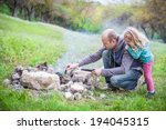 Small photo of Camping: Dad shows little daughter how to make a fire