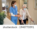 Smiling nurse with face mask helping senior woman to walk around the nursing home with walker. Young lovely nurse helping old woman with surgical mask for safety against covid-19 using a walking frame