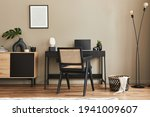 Small photo of Fancy interior design of home office space with stylish chair, desk, commode, black mock up poster frame, lapatop, book, desk organizer and elegant presonal accessories in home decor. Template.