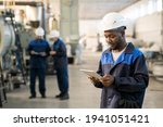 Young African male factory worker in overalls and hardhat using digital tablet while standing in front of camera against two busy colleagues