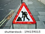 Small photo of triangular construction sign standing on footpath fto remind construction area ahead
