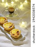 Small photo of three custards (Pasteis de nada) and an glassy espresso cup and illuminated glassy butterflies are in the bokeh of the baclkdrop.