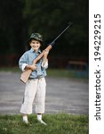 Small photo of little boy with airgun outdoors