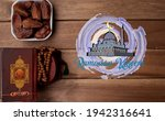A Ramadhan greeting poster with an illustration of a mosque,with dates druits,the Holy Quran,beads,over wooden background