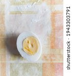 Small photo of boiled chicken egg, cut lengthwise, lies on a checkered tablecloth. View from above