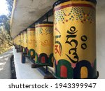 """Outdoor perspective shot of a row of yellow Tibetan Buddhist prayer wheels decorated with colourful symbols meaning """"Praise to the Jewel in the Lotus"""" on the path around the Dalai Lama temple, India"""