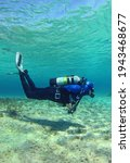 A Scuba Diver Dives From The...