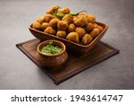 Small photo of Monsoon special Moong Dal Vada, Pakoda, Dalwada, Pakora or Mungdal Bhajiya or Yellow Split Gram Fritters Served with Green Chutney. selective focus