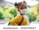 Small photo of Smiling cute little girl with school backpack and protective face mask ready for first day of school during covid pandemic. Black kid going back to school during coronavirus pandemic disease.