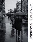 people walking with umbrellas... | Shutterstock . vector #1943777074