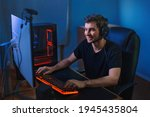 Small photo of Young professional gamer playing online video games on his PC. He is smiling because of winning the game, having live stream for his followers and subscribers. Cyber sport concept. Team play