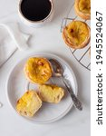 Small photo of Pastel de Nata - portugese egg custard pies on white marble background. Portuguese pasties on ceramic plate with spoon and coffee