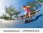 Small photo of Skateboarder in action. Young woman making trick on surf skate longboard in outdoor skatepark bowl. Surfskate and skateboard riding lessons at summer sport camp. Teens weekend recreational activities.