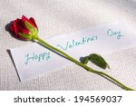 "Small photo of Red Rose lying on white cloth with a note ""Happy Valentines Day"" written on it"