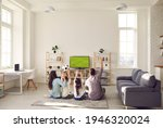 Small photo of Football match, leisure and happy family sport fan pastime together. Excited parent with overjoyed children watching soccer game on tv sitting on floor carpet in living room at home. Rear view