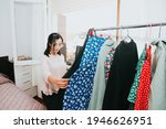 Small photo of Young arab woman checking his clothes at home during a super bright day, retail and resell concept