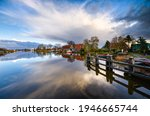 Small photo of Lake houses in village scene. Village lake houses reflection in lake water. Village lake view
