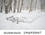 Snow Covered Wooden Bench In A...