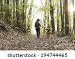 Stock photo young woman walking with dog in forest 194744465
